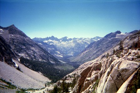 a valley between granite mountains within Yosemite Valley that fade into distant snowy mountains