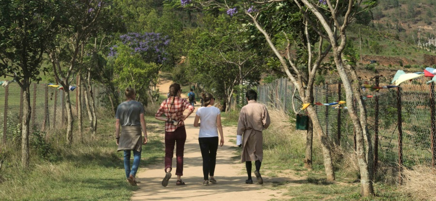 four people, wearing a a white t-shirt, red pants, a flannel shirt, and a traditional Bhutanese gho, walking along a path toward a monastery in Bhutan.